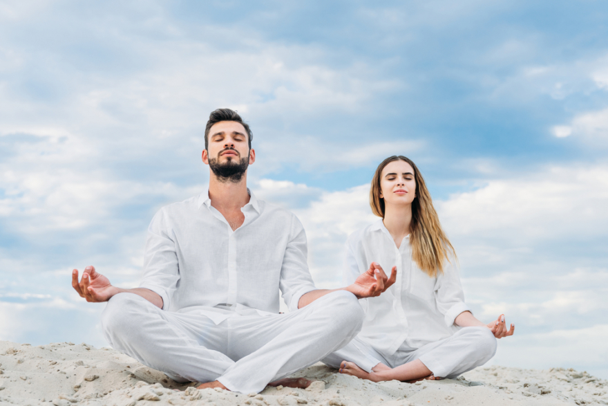 calm young couple meditating on a sandy dune
