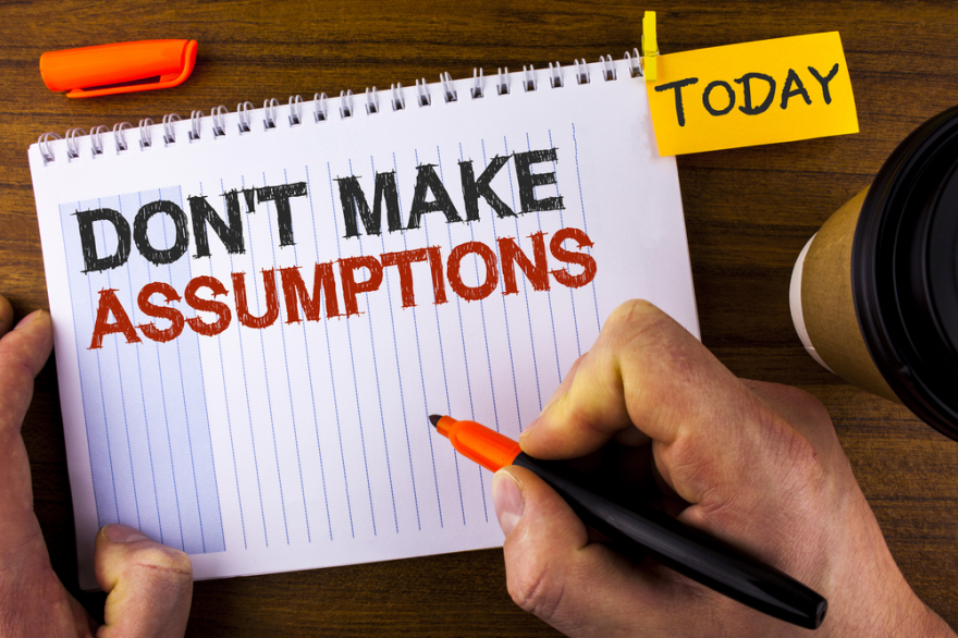 don't make assumptions written on note pad