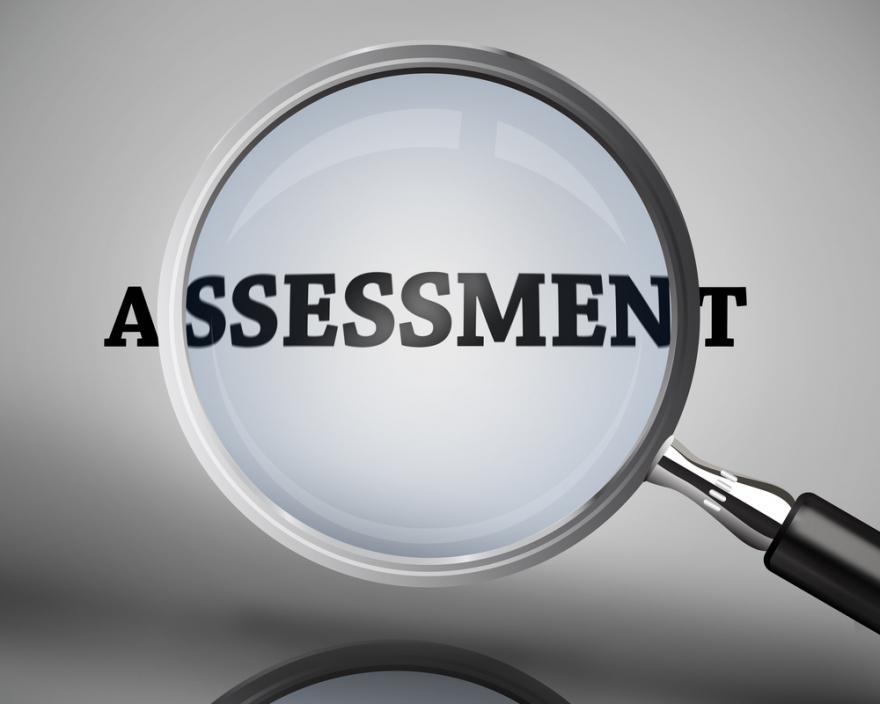 Magnifying glass highlighting word assessment