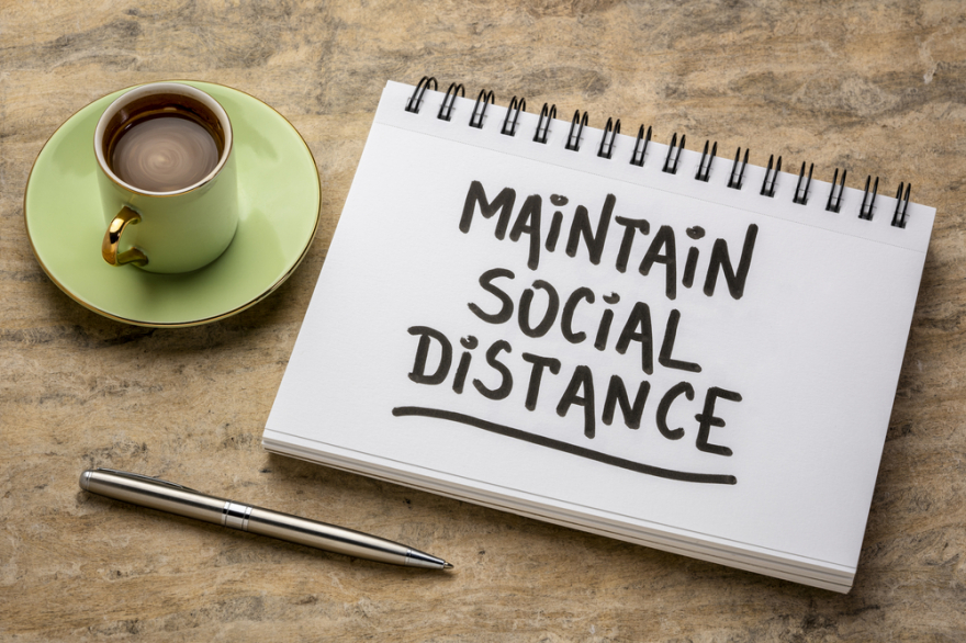 Maintain social distance written on a notepad