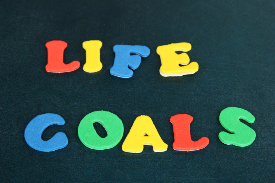 Phrase Life Goals written on blackboard in bright letters close up