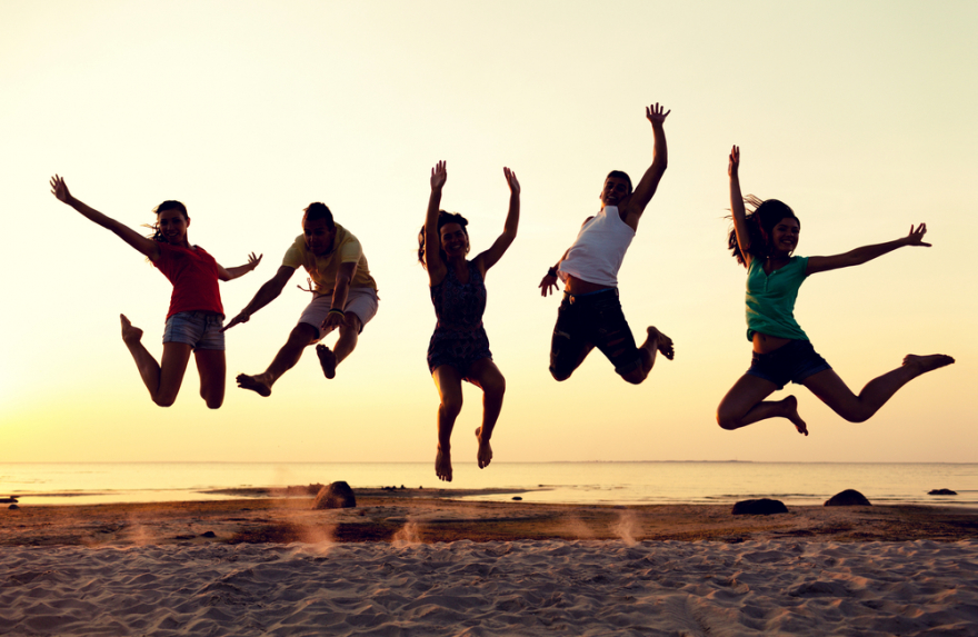 smiling friends dancing and jumping on the beach